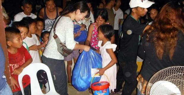 フィリピン台風被災地の支援6 配給品を手渡す松井さん
