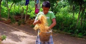 縄を編む前に椰子の繊維をほぐす少年