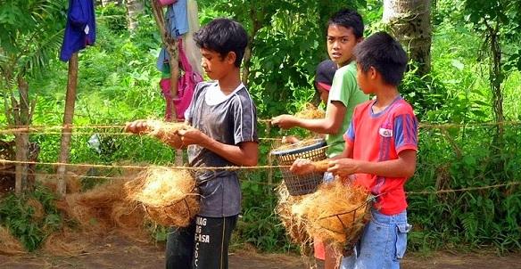 繊維を縒って縄を編んでいく少年達