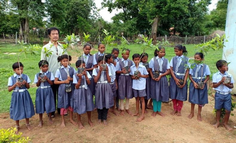 植樹の苗を持つ子どもたち